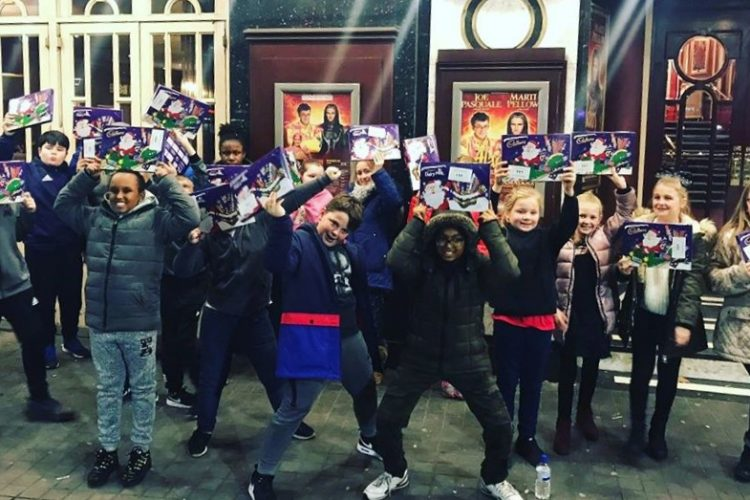 Young carers stand outside Bristol Hippodrome holding chocolate selection boxes.