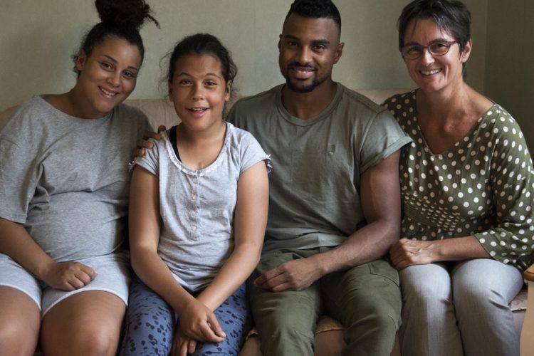 carer family sat against green background